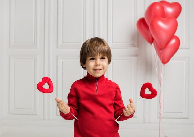 Mooie jongen die twee harten op een stok op een witte achtergrond met ballonsharten houdt
