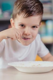 Mooie jongen eet melk pap. leuke baby die ontbijtzitting heeft bij een lijst in de keuken thuis.
