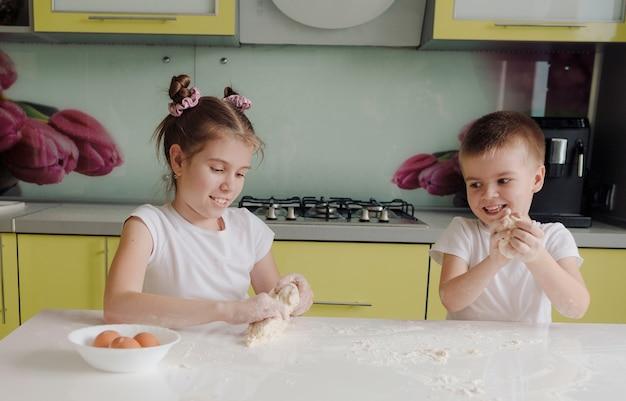 Mooie jongen en meisje deeg uitrekken in de keuken zijn rommelen en plezier hebben tijdens het koken. gelukkige blije kinderen