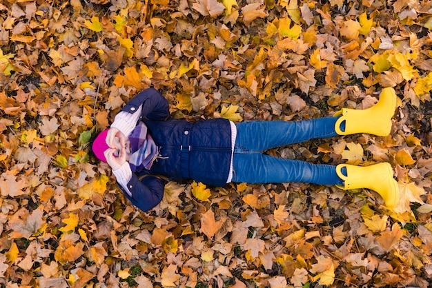 Mooie jongen in herfst park op gebladerte weergave. meisje lag bij bladeren en toont hart. uitzicht van boven.