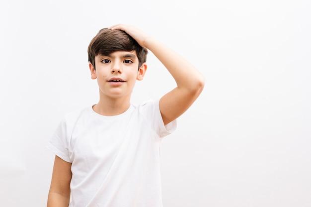 Mooie jongen jongen draagt casual wit t-shirt staande over geïsoleerde witte achtergrond verrast met hand op hoofd voor fout, onthoud fout. vergeten, slecht geheugenconcept.