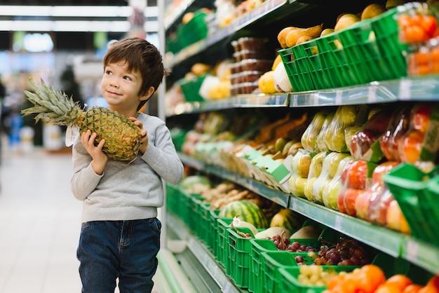 Mooie jongen met ananas in supermarkt