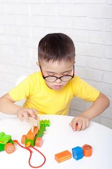 Mooie jongen met het syndroom van down sorteert geometrische vormen.