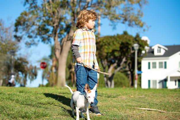 Mooie jongen met hond die buiten loopt. kind met haar huisdierenvriend.
