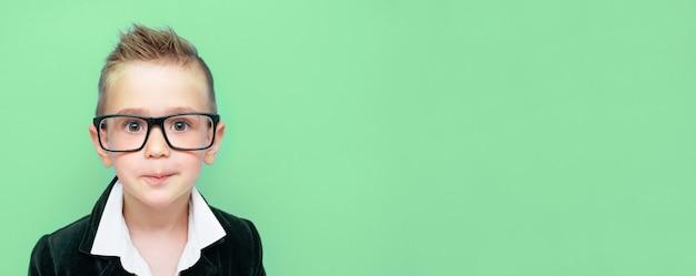 Mooie jongen met zwarte jas, wit t-shirt en bril op ogen geïsoleerd op groen oppervlak met kopie ruimte