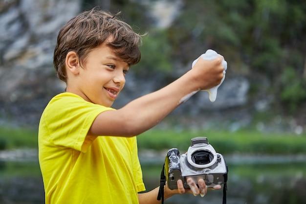 Mooie jongen reinigt cmos-beeldsensor in dslr-camera met zeepsop en water uit de rivier.