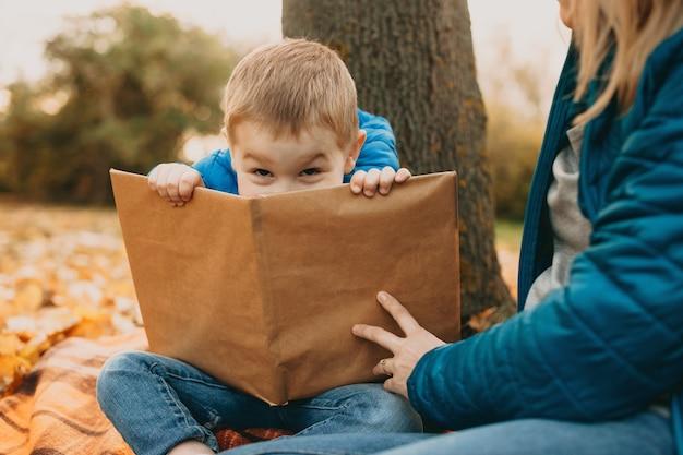 Mooie jongen speelt met zijn moeder terwijl hij een boek vasthoudt en zich verstopt terwijl hij buiten is.