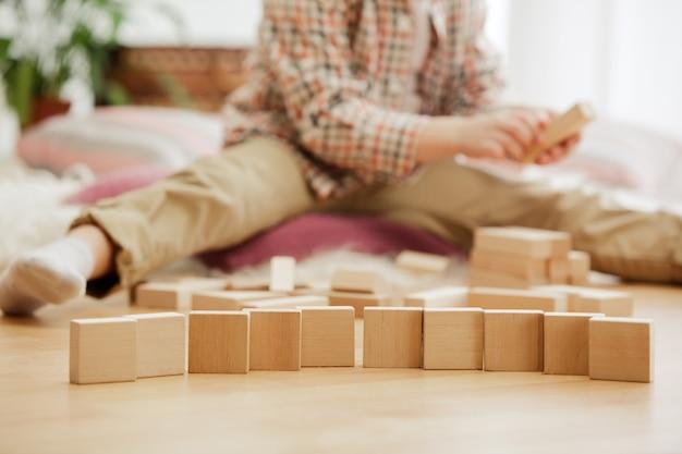 Mooie jongen thuis spelen met houten blokjes