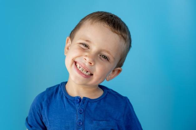 Mooie jongen toont tong en heeft plezier over blauwe muur achtergrond.