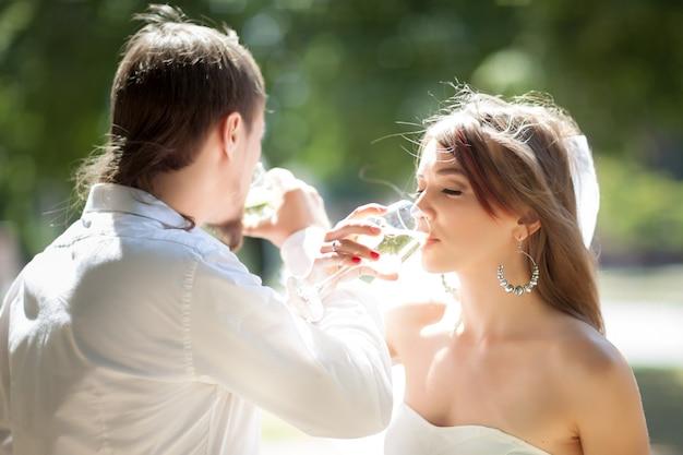 Mooie jonggehuwden drinken champagne buitenshuis.