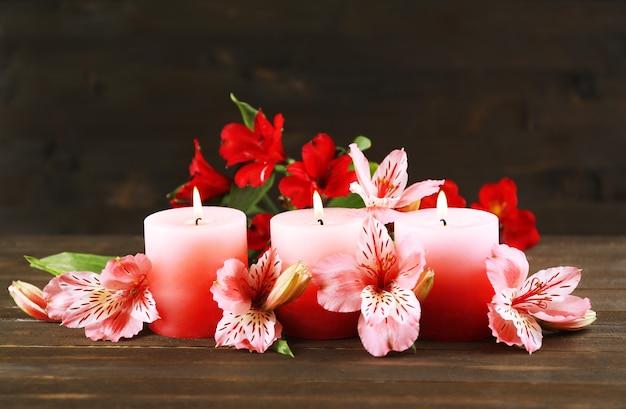 Mooie kaarsen met bloemen op houten tafel, op donkere achtergrond
