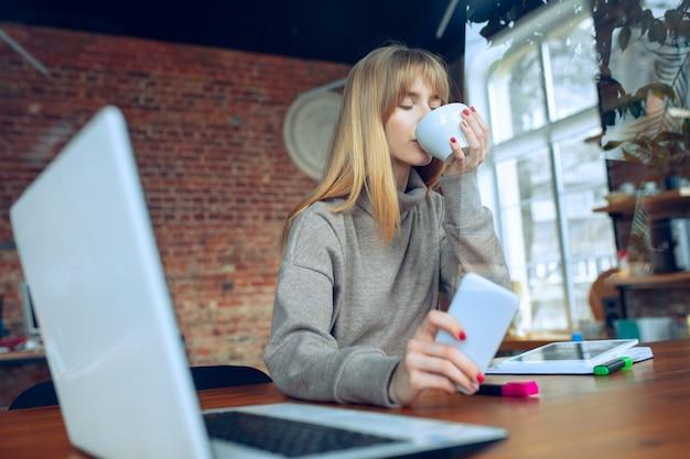 Mooie kaukasische bedrijfsdame die in bureau met laptop werkt