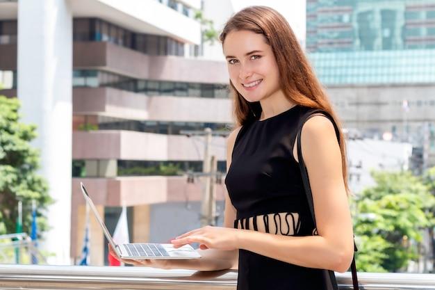 Mooie kaukasische bedrijfsleidervrouw die en over succeswerk glimlacht denkt. dame met laptop in zwarte reeks.