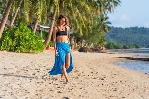 Mooie kaukasische brunette meisje op het tropische zandstrand in de buurt van zee, thailand, close-up. natuur en zomer concept