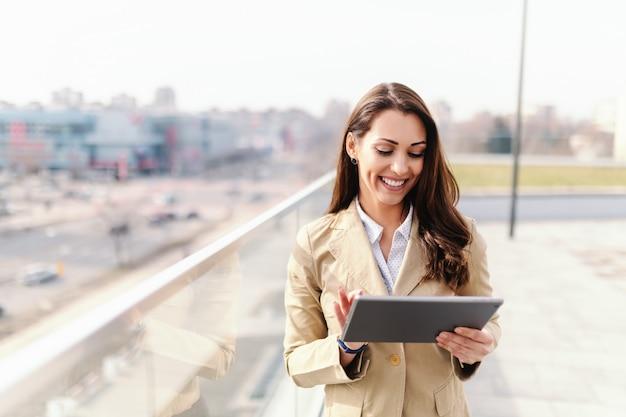 Mooie kaukasische brunette met brede glimlach en geklede slimme toevallige gebruikende tablet op dak.
