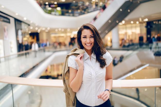 Mooie kaukasische brunette met grote brede glimlach in shirt poseren in winkelcentrum met haar beige jas over de schouder.
