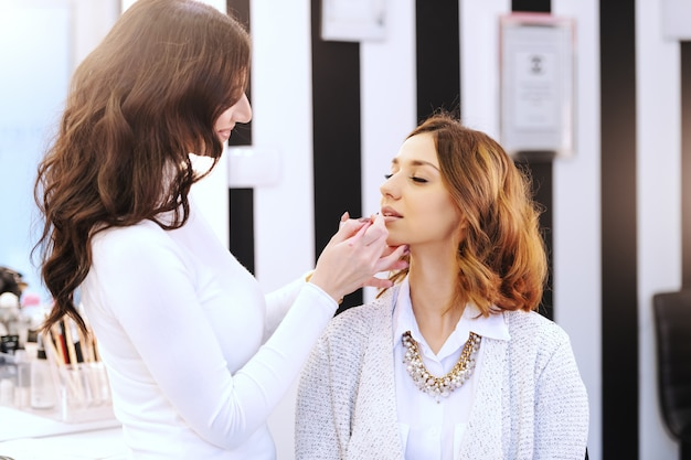 Mooie kaukasische brunette zitten in de schoonheidssalon terwijl make-up artiest lippenstift op haar lippen zetten.