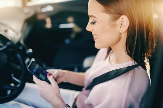 Mooie kaukasische brunette zitten in haar auto en het gebruik van slimme telefoon voor het lezen of verzenden van bericht.