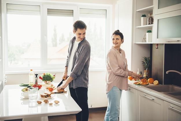 Mooie kaukasische coupé die naar elkaar glimlacht terwijl ze samen eten bereiden in de keuken