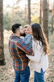 Mooie kaukasische familie, knappe bebaarde vader, mooie brunette vrouw moeder en schattige zoontje, plezier tijdens het wandelen in een herfst dennenbos