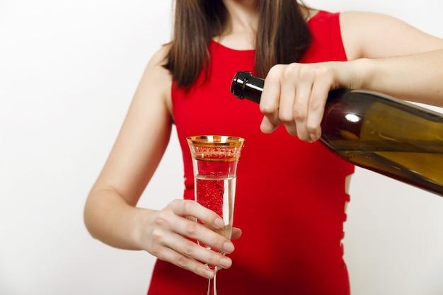 Mooie kaukasische gelukkige vrouw met charmante glimlach in rode jurk champagne uit fles gieten in het glas op witte achtergrond. santa meisje geïsoleerd close-up. nieuwjaar 2018 en kerstvakantie.