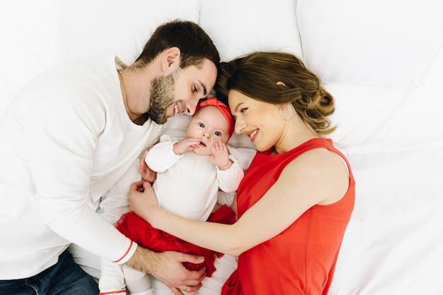 Mooie kaukasische gezin van drie op bed samen knuffelen