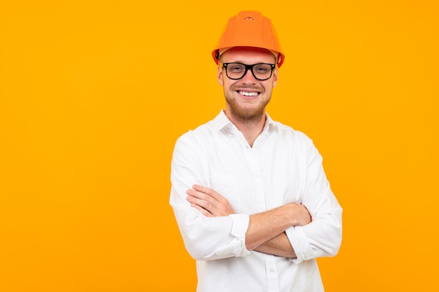 Mooie kaukasische ingenieursmens met glazen en oranje helm die op geel wordt geïsoleerd