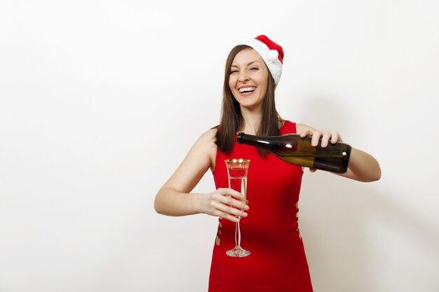 Mooie kaukasische jonge gelukkige vrouw met charmante glimlach in rode jurk en kerstmuts champagne uit fles gieten in het glas op witte achtergrond. santa meisje geïsoleerd. nieuwjaar 2018 vakantie