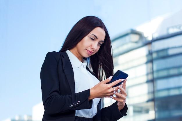Mooie kaukasische jonge onderneemster die haar celtelefoon bekijkt, die een bericht openlucht in een de zomerdag leest. formeel geklede vrouw met lange nagels met behulp van smartphone buiten.