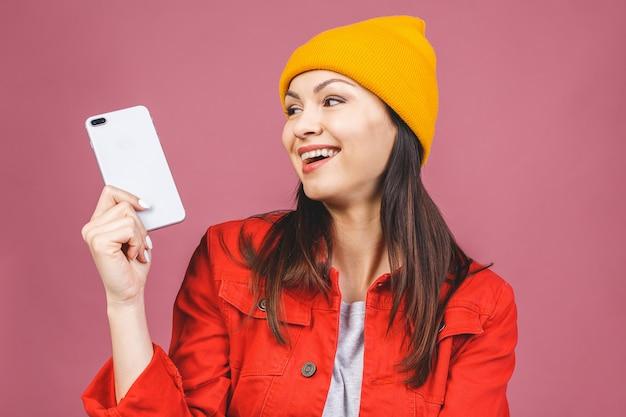Mooie kaukasische jonge vrouw met mobiele telefoon, poseren voor selfie, op zoek met flirterige glimlach. aantrekkelijke vrouw die videogesprek voert. geïsoleerd over roze muur.