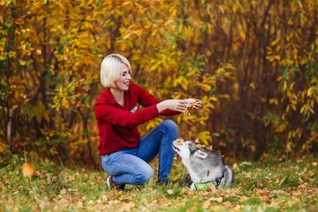Mooie kaukasische meisjesspelen met schor hond in de herfstbos