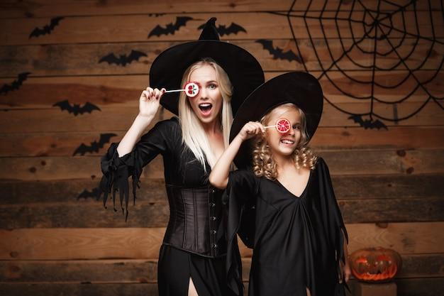 Mooie kaukasische moeder en haar dochter in heks kostuums vieren halloween met halloween snoep