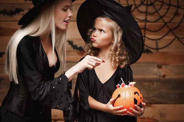 Mooie kaukasische moeder en haar dochter in heks kostuums vieren halloween met het delen van halloween snoep