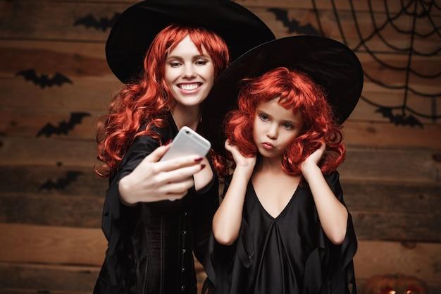 Mooie kaukasische moeder en haar dochter met lang rood haar in heksen kostuums nemen een selfie