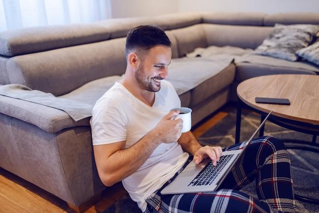 Mooie kaukasische ongeschoren lachende man zittend op de vloer in de woonkamer, surfen op internet en koffie drinken in de ochtend.