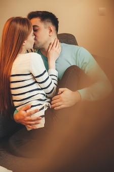 Mooie kaukasische paar kussen elkaar zittend op de bank en omhelzen in het zonlicht