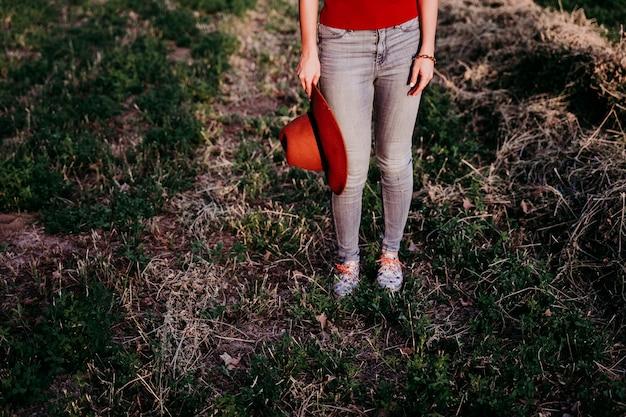 Mooie kaukasische vrouw die een bruine hoed houdt bij zonsondergang in platteland. levensstijl buitenshuis. van dichtbij bekeken