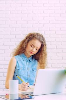 Mooie kaukasische vrouw die en aan laptop zit werkt
