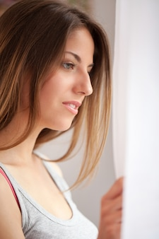 Mooie kaukasische vrouw die venster bekijkt