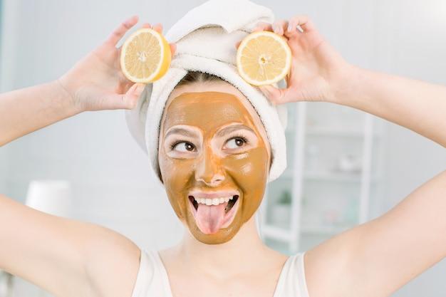 Mooie kaukasische vrouw in witte handdoek met bruin kleimasker op haar gezicht en citroenplakken, die tong en kusgezicht tonen, het concept van schoonheidsbehandelingen