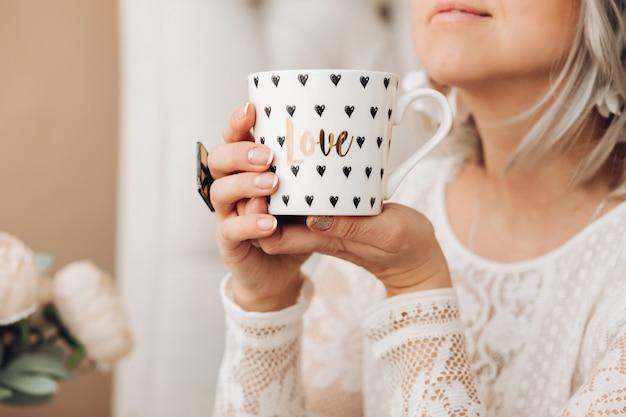 Mooie kaukasische vrouw met kort blond haar in witte trui houdt een witte kop koffie of thee, drinkt het en ligt op de bank