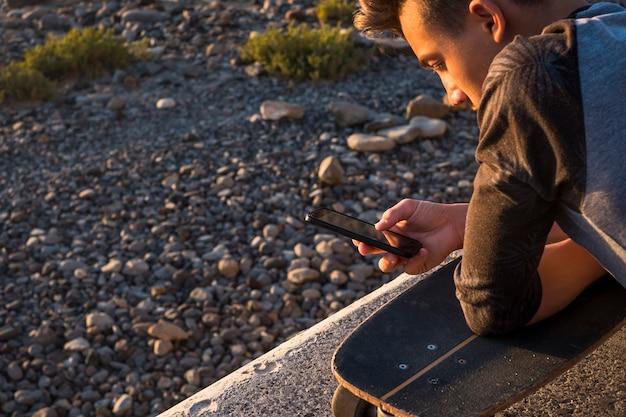 Mooie kerel en tiener op het strand alleen met zijn telefoon - spelen, chatten of video's bekijken met zijn skateboard