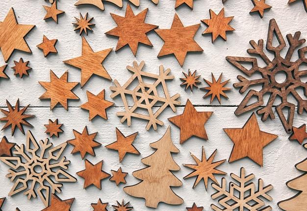 Mooie kerst achtergrond met veel kleine houten decoraties op wit houten bureau.