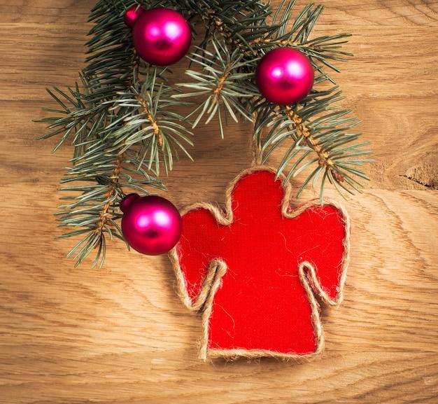 Mooie kerst engel met vuren takken op houten achtergrond