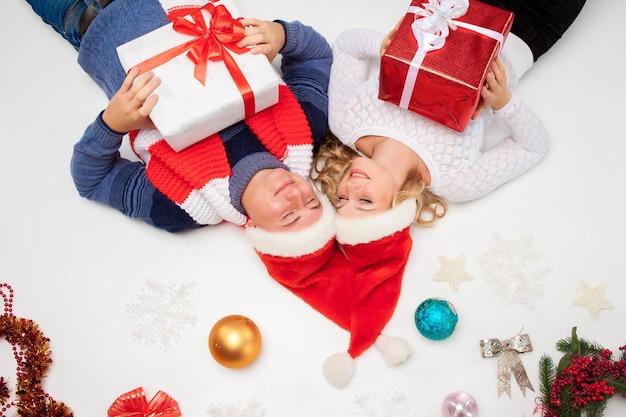 Mooie kerst paar in santa claus hoeden liggen met cadeautjes op witte achtergrond