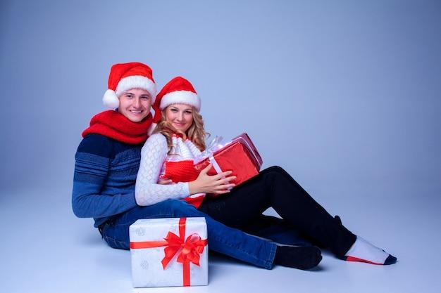 Mooie kerst paar in santa claus hoeden zitten met cadeautjes op blauwe achtergrond