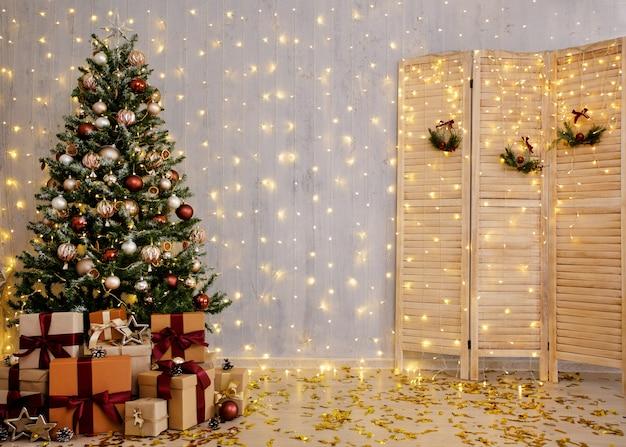 Mooie kerstachtergrond met boom, geschenkdozen, kamerscherm en feestelijke verlichting