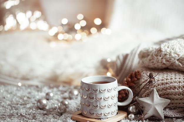 Mooie kerstbeker met een warme drank op een lichte onscherpe achtergrond. concept van huiscomfort en warmte.