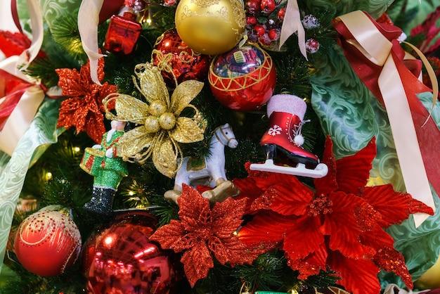 Mooie kerstboom met decor als achtergrond kerstverlichting versierd met ballen op boom in c...