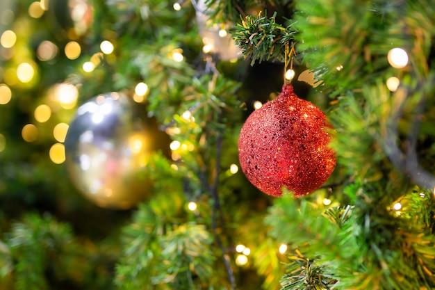 Mooie kerstboom met decor tegen vage bokeh lichten op achtergrond.